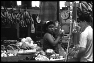 Thumbnail of Woman bagging produce at a market stall in the old marketplace, Belize City