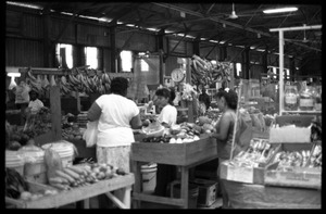 Thumbnail of Shopper examining produce, vendors, in the old marketplace, Belize City