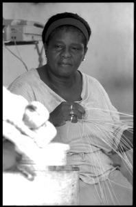 Thumbnail of Woman (H. N. Cove) seated by a table in her store, plaiting palm leaf baskets, Belize City