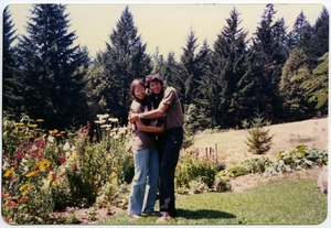 Thumbnail of Love Sandwich:  Mark and Sandi Sommer with Chewie in between, on lawn, Salmon Creek