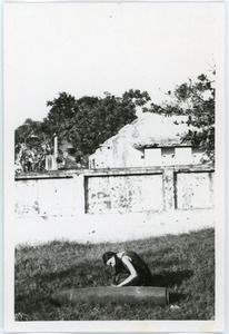 Thumbnail of Naomi Jaffe examining unexploded bomb, in front of ruins
