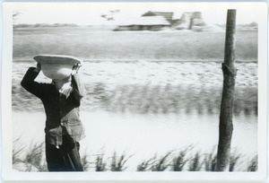 Thumbnail of Woman holding pith helmet beside rice paddy