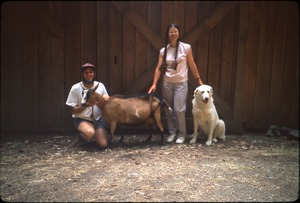 Thumbnail of Mark and Sandi Sommer in front of barn with Maya the dog and Kate (mama goat)