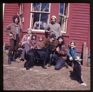 Thumbnail of Nina Keller (far left) and her mother, Janice Frey (far right), and others,             seated in front of the house at Montague Farm Commune with dogs