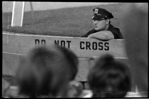 Thumbnail of Beatles concert at Shea Stadium: Policeman providing concert security, leaning             on a barrier reading 'Do not cross'