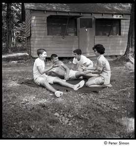Thumbnail of Camp Arcadia: campers seated on a blanket in front of a cabin