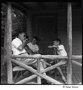 Thumbnail of Camp Arcadia: camper talking with adults, seated on a cabin porch