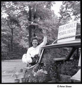 Thumbnail of Andrea Simon: waving beside car, holding flowers by sign that reads, 'Riverdale Mental Health Association'
