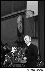 Thumbnail of Presidential candidate Eugene McCarthy behind a bank of microphones giving a speech at Boston University View showing basketball hoop behind the podium
