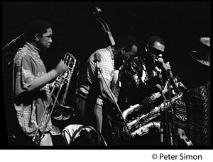 Thumbnail of Roland Kirk Quartet in performance, Newport Jazz Festival L. to r.: Dick Griffin (trombone), Vernon Martin (bass), Rahsaan Roland Kirk             (saxophone), and Joe Texidor (back to camera)