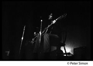 Thumbnail of Tim Buckley in performance, probably at the Unicorn Coffee House Buckley on stage with guitar (Lee Underwood in background)