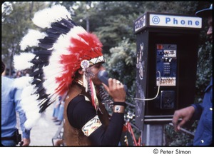 Thumbnail of MUSE concert and rally: man in Native American ceremonial dress talking on a payphone