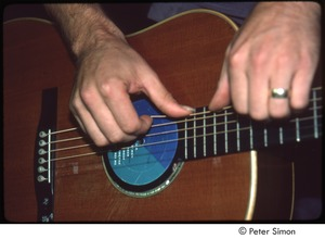 Thumbnail of MUSE concert and rally: James Taylor's hands on his guitar, backstage at the MUSE concert