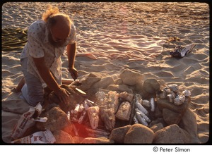 Thumbnail of Ram Dass cooking fish and corn over an open fire on the beach