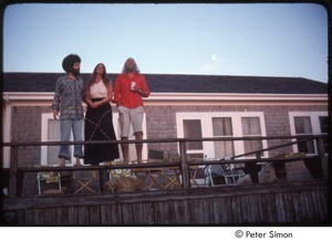 Thumbnail of Ram Dass (right), Mirabai Bush, and Daniel Goleman on a beach house deck