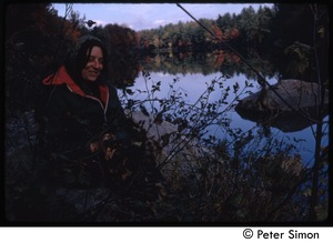 Thumbnail of View of a woman seated by the edge of a pond, Tree Frog Farm commune