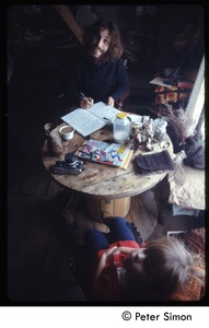 Thumbnail of Elliot Blinder seated at a table, with child, Tree Frog Farm commune