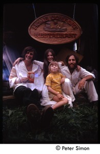 Thumbnail of TIm Rossner(?), Catherine Blinder, Elliot Blinder and child (l. to r.) seated under sign for             Home Comfort Restaurant, Tree Frog Farm commune