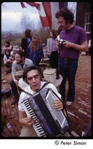 Thumbnail of Harry Saxman (purple shirt) with man playing an accordion at May Day celebration, Packer Corner's             commune