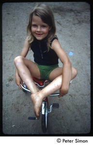 Thumbnail of Young girl on a tricycle, Tree Frog Farm commune