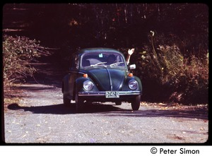 Thumbnail of Volkswagen beetle driving down the road, Tree Frog Farm commune