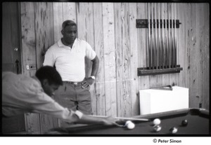 Thumbnail of Party at Jackie Robinson's house: man playing pool while Jackie Robinson watches