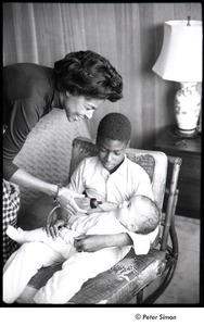 Thumbnail of Party at Jackie Robinson's house: Rachel Robinson showing David Robinson how to feed a baby with a bottle