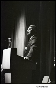 Thumbnail of Martin Luther King Jr. rally at the Fieldston School: Ossie Davis speaking, Ruby Dee (partially obscured) seated on right