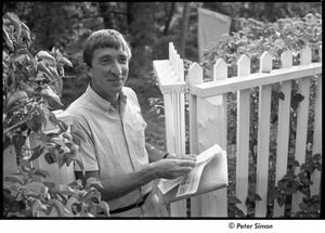 Thumbnail of John Updike portrait with newspaper