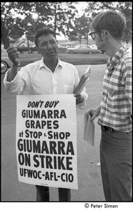 Thumbnail of UFOWC grape pickers strike at Stop and Shop: protestor gesturing with corn cob pipe and talking to BU News reporter Paul Trowbridge