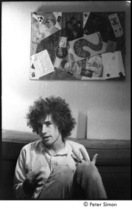 Thumbnail of Tim Buckley at the Catacombs: Buckley backstage, seated on the floor with a collage in the background