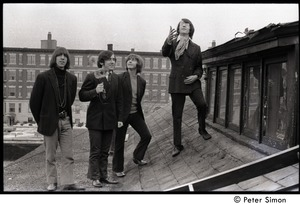 Thumbnail of The  Orphans (Boston rock group): posed on a rooftop, tossing paper flowers