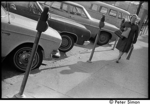 Thumbnail of Woman walking past a row of parking meters and parked cars on the street
