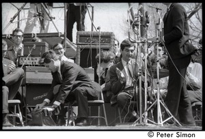 Thumbnail of Resistance on the Boston Common: Staughton Lynd seated on the dais, reaching into a             bag, Howard Zinn to his left clapping