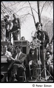 Thumbnail of Resistance on the Boston Common: Terry Cannon (draft resister and member of the             Oakland 7) addressing the crowd, Howard Zinn  checking his notes on stage (far left)