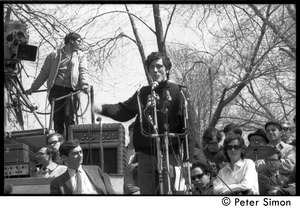 Thumbnail of Resistance on the Boston Common: Terry Cannon (draft resister and member of the             Oakland 7) addressing the crowd, Howard Zinn seated on stage (far left)