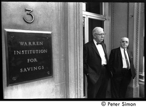 Thumbnail of Two older men watching the march commemorating Martin Luther King, standing in the entrance to the Warren Institute of Savings (3 Park Street)