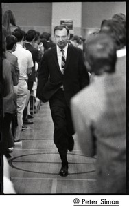 Thumbnail of Man leading the entourage of presidential candidate Eugene J. McCarthy up an             aisle before a speech at Boston University