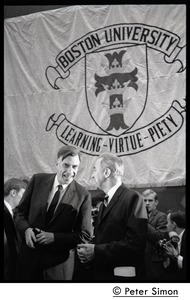Thumbnail of John Kenneth Galbraith (left) talking with presidential candidate Eugene             McCarthy on dais at Boston University, in front of a large BU banner