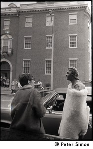 Thumbnail of Umoja (Black student union) activist standing by car, wrapped in a sheepskin and talking to a white             onlooker, at site of occupied administration building, Boston University