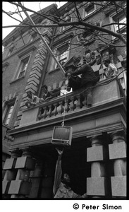 Thumbnail of Umoja (Black student union) activists hoisting a television to occupiers             of the administration building, Boston University