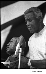 Thumbnail of Jackie Robinson at the microphone, holding a bust of Martin Luther King