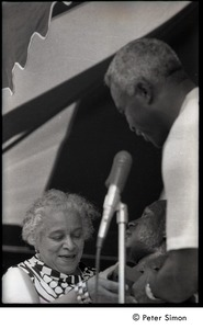 Thumbnail of Jackie Robinson at the microphone, presenting a bust of Martin Luther King to             unidentified woman