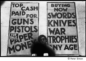 Thumbnail of Kim Rosen standing in front of a sign at a curio store 'Top cash paid for guns...'