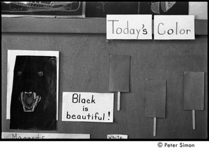 Thumbnail of Bulletin board at the Liberation School, with signs reading 'Today's color' and             'Black is beautiful' and a student drawing of black panther