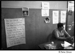 Thumbnail of Teacher seated at a table at the Liberation School: in front of a poster             honoring Martin Luther King: 'He tried to help everbody in the city. He died. Somebody             shot him...'