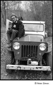 Thumbnail of Raymond Mungo seated on the hood of a Willys jeep, Packer Corners Commune