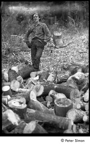Thumbnail of Raymond Mungo posed by a stack of sawn wood, waiting to be split: Packer Corners commune