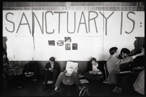 Thumbnail of Protesters at the Sala de Puerto Rico seated under banner reading 'Sanctuary is' : Vietnam War sanctuary at MIT
