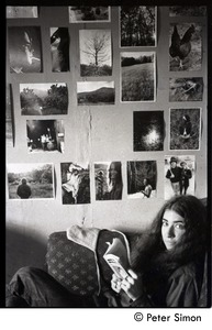Thumbnail of Sarah, seated and reading in front of a wall of commune photographs, Packer Corners commune
